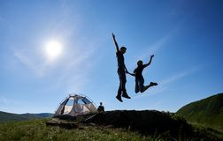 Happy couple jumping on blue sky background with bright sun near camping in mountains stock photos