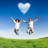 Happy couple jumping. In green field against blue sky. Summer vacation concept Royalty Free Stock Photos