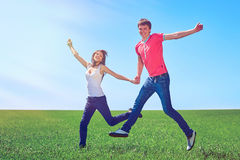 Happy couple jumping in green field. Happy couple jumping of joy in green field against blue sky Stock Images