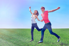 Happy couple jumping in green field. Happy couple jumping of joy in green field against blue sky Royalty Free Stock Photography