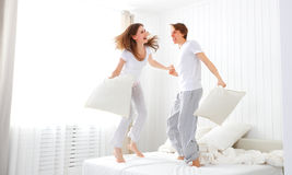 Happy couple jumping and having fun in bed. Happy loving couple jumping and having fun in bed