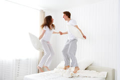 Happy couple jumping and having fun in bed Royalty Free Stock Image