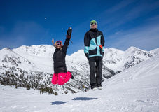 Happy couple jumping in mountains. Happy couple jumping on the background of snowy mountains Stock Photo
