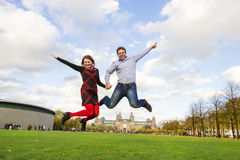 Happy couple jumping in Museumplein, Amsterdam Stock Photos