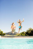 Happy couple jumping in the pool Royalty Free Stock Photo