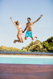 Happy couple jumping in the pool Royalty Free Stock Photography