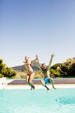 Happy couple jumping in the pool Stock Photography