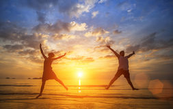 Happy  couple jumping in Sea beach during a beautiful sunset. Happy young couple jumping in Sea beach during a beautiful sunset Stock Photos