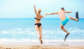 Happy couple jumping in the sea stock photos