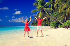 Happy couple jumping on the summer beach. Happy couple jumping on the summer tropical beach Royalty Free Stock Images