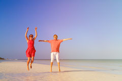 Happy couple jumping on the summer beach. Happy couple jumping on the summer tropical beach Stock Photos