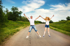 Happy couple jumping. Summer outdoor Royalty Free Stock Image