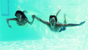Happy couple jumping in swimming pool together Royalty Free Stock Images