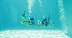 Happy couple jumping into swimming pool wearing snorkels and holding starfish stock video footage