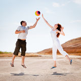 Happy couple jumping to catch a ball Royalty Free Stock Images
