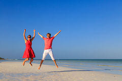 Happy couple jumping on the tropical beach. Happy couple jumping on the summer tropical beach Stock Photo