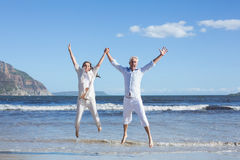 Happy couple jumping up barefoot on the beach Royalty Free Stock Image