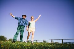 Happy couple jumping and waving. Happy couple jumping on the grassfield and waving. Active retirement. Mature relationship Stock Images