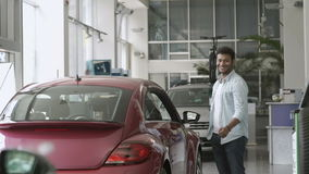 Happy couple just bought a car in car dealership. Happy swarthy guy looks in camera and smiling. He shows a thumb up. Pretty girl appears from car`s window and stock video