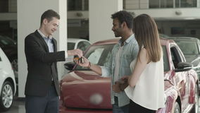 Happy couple just got a keys from a new car in car showroom. Young couple choose the car in car showroom. The manager in suit gives the keys from car to a stock video footage