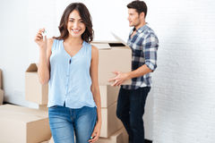 Happy couple with key and boxes moving to new home. Happy married couple with key and boxes moving to new home Stock Photos