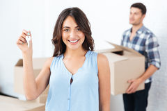 Happy couple with key and boxes moving to new home Stock Photos