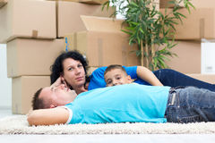 Happy couple with a kid in their new home laying on the floor Stock Photo