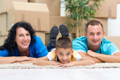 Happy couple with a kid in their new home laying on the floor wi Royalty Free Stock Images