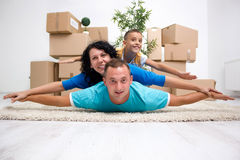 Happy couple with a kid in their new home laying on the floor wi. Couple with a kid in their new home laying on the floor royalty free stock images
