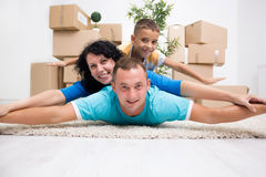 Happy couple with a kid in their new home laying on the floor wi. Happy couple with a kid in their new home laying on the floor stock photos