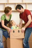 Happy couple with a kid unpacking in a new home Stock Photography