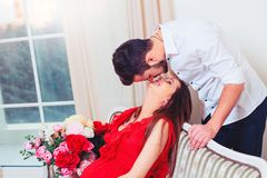 Happy couple kiss in the living room having Stock Photography