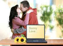 Happy Couple Kissing. Focus is on the laptop. Man and woman are blurred Royalty Free Stock Photography