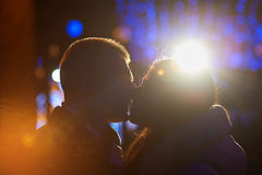 Happy couple kissing on the background of illuminations and bokeh.  Royalty Free Stock Photo