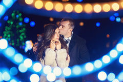 Happy couple kissing on the background of illuminations and bokeh.  Stock Photos