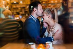 Happy couple kissing at bar and having date Stock Photo
