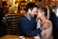 Happy couple kissing at bar and having date Stock Images