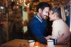 Happy couple kissing at bar and having date. Happy attractive couple kissing at bar having date Stock Images