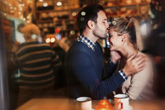 Happy couple kissing at bar and having date. Happy attractive couple kissing at bar having date Royalty Free Stock Image