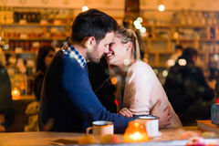 Happy couple kissing at bar and having date Royalty Free Stock Images