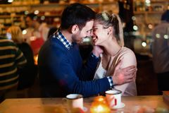 Happy couple kissing at bar and having date stock image