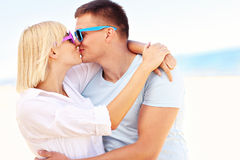 Happy couple kissing at the beach Stock Images
