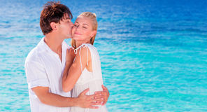 Happy couple kissing on the beach. Young family in love spending honeymoon vacation on an islands, cheerful active young people having fun at summer travels Royalty Free Stock Photo