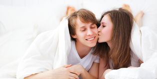 Happy couple kissing in bed peeking out from under blanket Royalty Free Stock Images