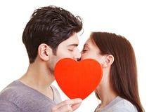 Happy couple kissing behind heart. Happy couple kissing behind a red heart Stock Photo