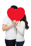 Happy couple kissing behind heart Stock Image