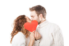 Happy couple kissing behind a red heart Royalty Free Stock Images