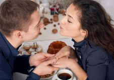 Happy couple kissing and drinking tea indoor.  Royalty Free Stock Photos