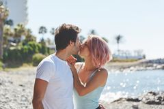 Happy couple kissing each other on beach. Profile portrait of happy couple kissing each other on beach Stock Images