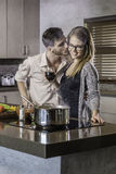 Happy couple kissing and flirting while cooking a meal in the kitchen Stock Images